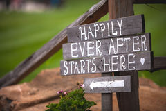 Começa felizmente para sempre aqui o sinal no local de encontro do casamento imagem de stock royalty free