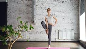 Começar o estudante fêmea da ioga está fazendo a sequência de exercícios do equilíbrio na classe linear da ioga É às vezes inábil filme