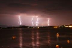 Começo de uma tempestade em um mar com relâmpagos no céu roxo Fotografia de Stock