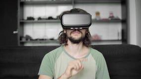 Começo farpado novo do homem do moderno usando sua exposição dos auriculares de VR para a navegação no jogo do vr-programa ou da