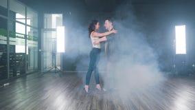 Começos do fumo que enchem a sala quando um par começar a dançar em um estúdio video estoque