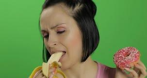Come?ando comer saud?vel Diga n?o ? comida lixo Filh?s ou banana bem escolhida a comer fotografia de stock