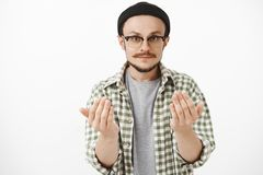Come on closer. Serious-looking skilfful artistic bearded guy in glasses and black beanie raising palms near body asking. Approach to him or give something royalty free stock photo