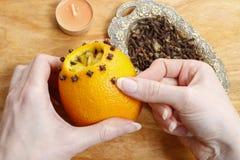 Come fare la palla arancio del pomander con la candela - esercitazione Immagini Stock