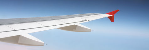 Come fly with me. An airplane wing against a blue sky Royalty Free Stock Photo