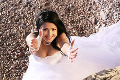 Come here. Portrait of beautiful young bride on the sea coast. She pulls up her hands Stock Image