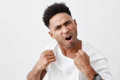Come here and fight me if you dare. Close up of mature aggressive attractive dark-skinned man with curly hair in white. Tshirt being ready to fight, angry Stock Photos