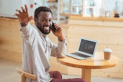 Overjoyed man greeting someone while talking on phone Stock Image