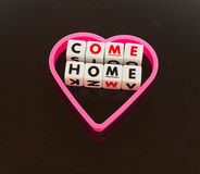 Come home sweetheart. Text 'Come home' inscribed in  uppercase letters on small white cubes inside a heart shape on a dark background Royalty Free Stock Images