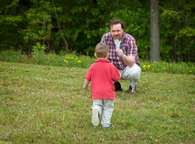 Come Make a Wish. Father holding a dandelion while his son, a young boy, walks towards him. Focus is on the boy royalty free stock images