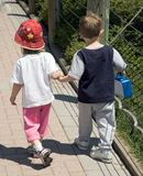 Come With Me Dear... A little boy and girl holding hands while walking. She appears to be leading the way Stock Image
