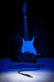 Come out and play. Electric guitar on blue background and plug in spotlight Stock Images