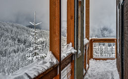 Snowy Balcony on Alpine Hut on Cloudy Day. Balcony of Volunteer Run Mountain Shelter Offers Sanctuary from Winter's Cold Royalty Free Stock Image