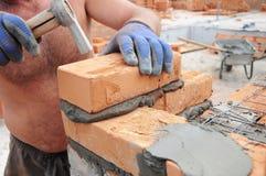 Come porre i mattoni: Muratore che pone i mattoni con il martello Costruzione di muratura fotografia stock