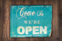 Come in we're open sign on an old wooden background Stock Photos