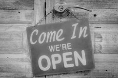 Come In We're Open on the wooden door, Black and white Photo.  Royalty Free Stock Photo