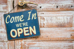 Come In We're Open on the wooden door, copyspace on the right Stock Photography