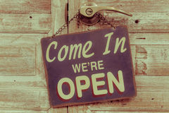 Come In We're Open on the wooden door, retro vintage style.  Royalty Free Stock Image