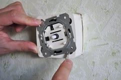 Come sostituire un interruttore della luce con un regolatore della luminosità immagini stock libere da diritti