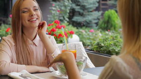 Come on tell me everything. Women on the terrace of a cozy cafe rejoices meeting stock video footage