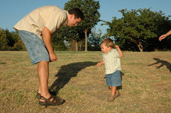 Come to daddy. Baby boy is learning how to walk towards his daddy in a park royalty free stock photography