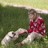 Come to mistress. Full body view of an older woman with pug dog and look to the dog sitting in the grass in the summer royalty free stock photos