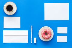 Come up with brand identity. Blank stationery for branding near coffee and donut on blue background top view mockup. Come up with brand identity. Blank Royalty Free Stock Photo