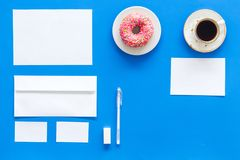Come up with brand identity. Blank stationery for branding near coffee and donut on blue background top view mockup. Come up with brand identity. Blank Royalty Free Stock Photos