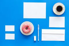 Come up with brand identity. Blank stationery for branding near coffee and donut on blue background top view mockup. Come up with brand identity. Blank Stock Photography
