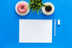Come up with brand identity. Blank stationery for branding near coffee and donut on blue background top view mockup. Come up with brand identity. Blank Stock Image