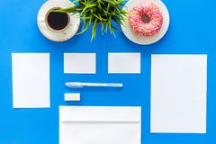 Come up with brand identity. Blank stationery for branding near coffee and donut on blue background top view mockup. Come up with brand identity. Blank stock images