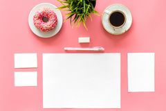 Come up with brand identity. Blank stationery for branding near coffee and donut on pink background top view mockup. Come up with brand identity. Blank Royalty Free Stock Photo
