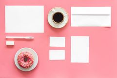 Come up with brand identity. Blank stationery for branding near coffee and donut on pink background top view mockup. Come up with brand identity. Blank Royalty Free Stock Images