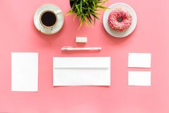 Come up with brand identity. Blank stationery for branding near coffee and donut on pink background top view mockup. Come up with brand identity. Blank Stock Photo