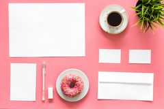 Come up with brand identity. Blank stationery for branding near coffee and donut on pink background top view mockup. Come up with brand identity. Blank royalty free stock image
