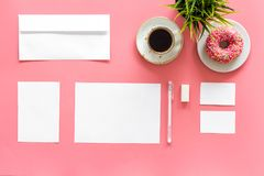Come up with brand identity. Blank stationery for branding near coffee and donut on pink background top view mockup. Come up with brand identity. Blank Stock Photos