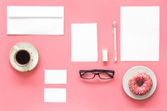Come up with brand identity. Blank stationery for branding near coffee and donut on pink background top view mockup. Come up with brand identity. Blank Stock Photography