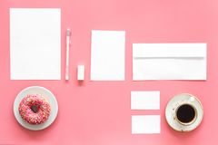 Come up with brand identity. Blank stationery for branding near coffee and donut on pink background top view mockup. Come up with brand identity. Blank Stock Image