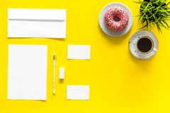 Come up with brand identity. Blank stationery for branding near coffee and donut on yellow background top view mockup. Pattern Stock Images