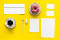 Come up with brand identity. Blank stationery for branding near coffee and donut on yellow background top view mockup. Pattern Royalty Free Stock Photography