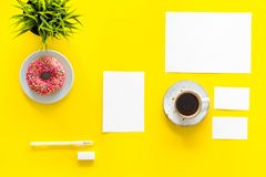 Come up with brand identity. Blank stationery for branding near coffee and donut on yellow background top view mockup. Pattern Royalty Free Stock Photos