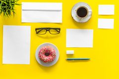 Come up with brand identity. Blank stationery for branding near coffee and donut on yellow background top view mockup. Pattern Stock Photos