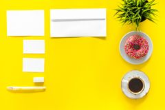 Come up with brand identity. Blank stationery for branding near coffee and donut on yellow background top view mockup. Pattern Royalty Free Stock Images