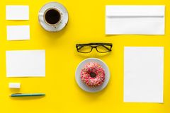 Come up with brand identity. Blank stationery for branding near coffee and donut on yellow background top view mockup. Pattern Royalty Free Stock Image