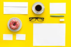 Come up with brand identity. Blank stationery for branding near coffee and donut on yellow background top view mockup. Pattern Stock Photography