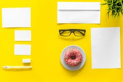 Come up with brand identity. Blank stationery for branding near coffee and donut on yellow background top view mockup. Pattern Royalty Free Stock Photo