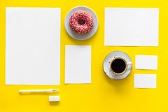 Come up with brand identity. Blank stationery for branding near coffee and donut on yellow background top view mockup. Pattern Stock Image