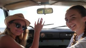 Come with us on car, two girl make hand gesture into automobile in sunlight, females waving inviting in joint trip. Background nature, young women on summer stock video