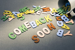 Comeback Soon. Wood letters spill out of the cup as Comeback Soon Royalty Free Stock Photography