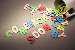 Comeback Soon. Wood letters spill out of the cup as Comeback Soon Royalty Free Stock Photo